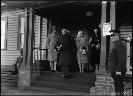 "Royal Visit, May 1927. Duke and Duchess of York with Prime Minister  Rt Hon S M Bruce at Canberra Railway Station Notice on the pillar reads ""Canberra Anglican Cathederal Site. Sunday May 8th Open Air Service""."
