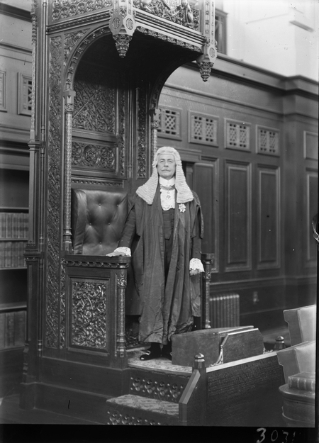 Royal Visit, May 1927. Sir Littleton Groom standing at the Speaker's Chair, House of Representatives Chamber.