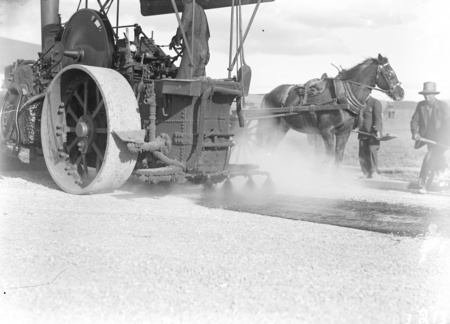 Steamroller fitted with tar spray at work, Mort Street, Canberra City. Horse and dray.
