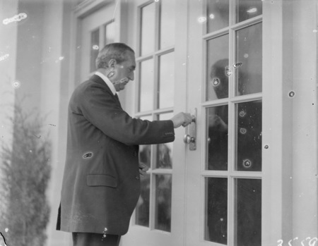 The Right Honorable Stanley Melbourne Bruce opening the front door of Ainslie School in September 1927.