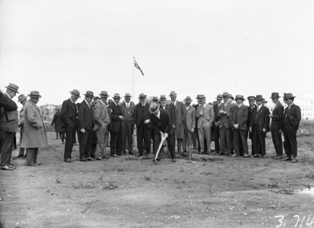 A crowd of onlookers with the Rt. Hon. Stanley Melbourne Bruce on shovel.