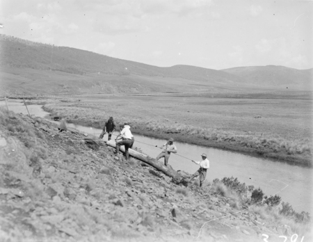 Four men erecting a power pole near the Monglo River.