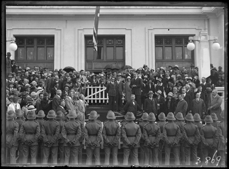 Bert Hinkler being welcomed by Prime Minister S.M. Bruce in front of Parliament House with Royal Military College Cadets and spectators.