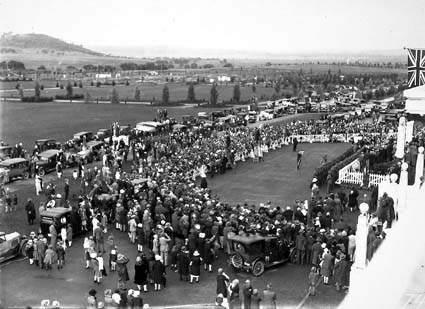 Bert Hinkler's welcome to Canberra by Prime Minister S.M.Bruce in front of Parliament House with large crowd of spectators