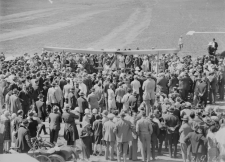 Crowd welcoming Captain W.N. Lancaster and Mrs Keith Miller and their Avro Avian aircraft G-EBIO at the Review Ground opposite Hotel Kurrajong.