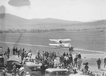 "Captain W.N. Lancaster and Mrs Keith Miller landing their Avro Avian G-EBIO ""Red Rose"" at the Review Ground opposite Hotel Kurrajong."