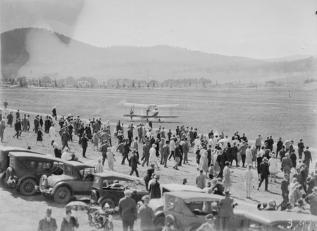 Arrival of Captain W.N. Lancaster and Mrs Keith Miller at the Review Ground opposite Hotel Kurrajong, aircraft taxing after landing.