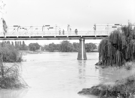 Commonwealth Bridge over the Monoglo River showing floodwaters and depth gauge.