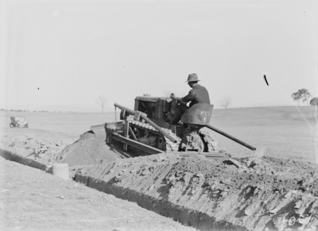International crawler tractor with scraper attachment filling earth into a trench.