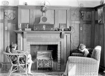 Sitting room with two girls reading, electric fire, wireless, wall lights and fan