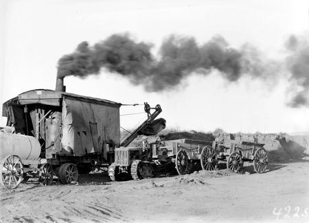 Keystone steam shovel loading wagons hauled by a Cletrac Tractor