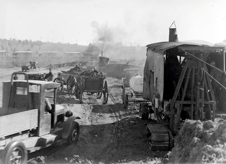 Keystone steam shovel and tractor towing two loaded  wagons and a motor truck