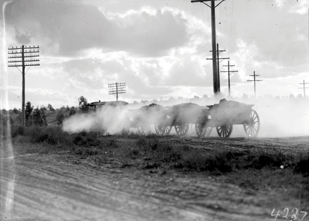Tractor towing two loaded  wagons. Details obscured by dust