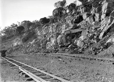Quarry face with narrow gauge  tram  tracks and a skip