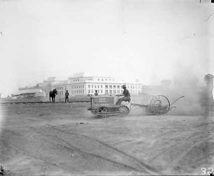 Parliament House opening preparations - Cletrac crawler tractor and scoop preparing the grounds - Light rail line in middle ground used to carry bricks from the brickworks to building sites