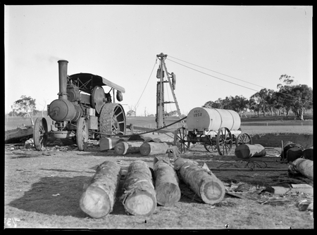 Steam traction engine operating a pile driver. Mobile water tank on right.
