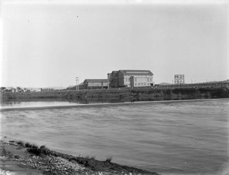 Kingston Power Station from the north bank of the Molonglo River, with weir in front.