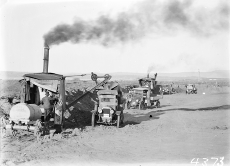 Two Keystone steam excavators loading motor trucks.
