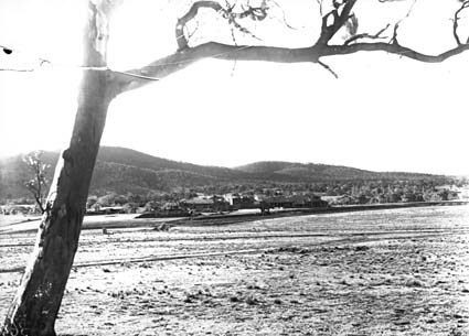 Hotel Canberra from the site of Parliament House with brickworks railway crossing Commonwealth Avenue after a snow fall