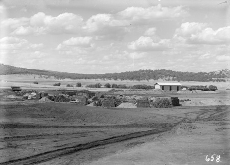 Parliament House site showing piles of bricks and construction material.