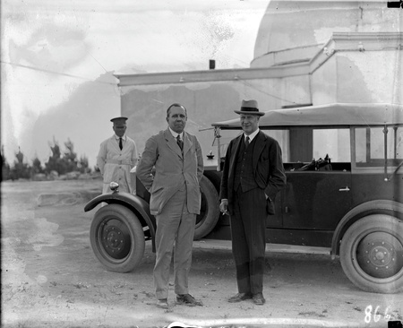 Commonwealth car and driver with two visitors at Mt Stromlo