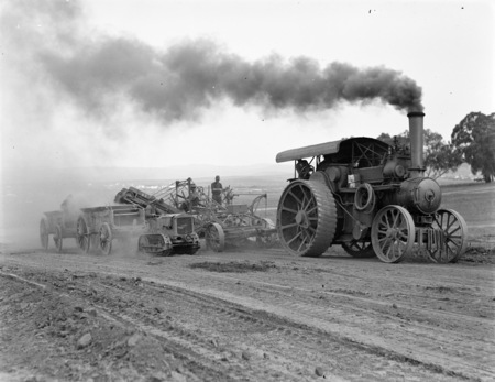 Traction engine towing a road grader loading a wagon and a Cletrac crawler tractor towing a wagon.