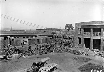 Parliament House under construction - Courtyard on House of Representatives side - East block and Hotel Kurrajong in background