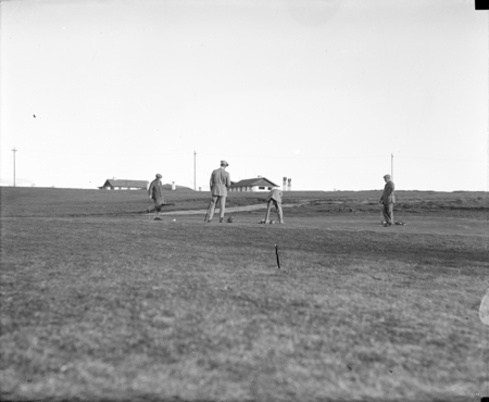 Four golfers on green, Canberra Hotel in background.