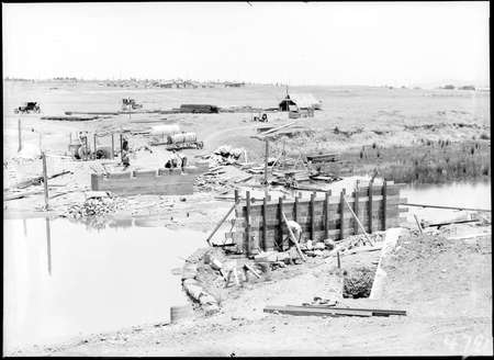 Scotts Crossing over the Molonglo River under construction looking south showing Molonglo camp and Blundells Cottage.