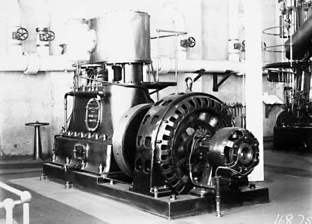Robey Hall 150 kW twin cylinder ,double expansion steam engine coupled to a 150 kW alternator at Kingston Power Station. Note: white steam lines in background delivering steam from the boilers