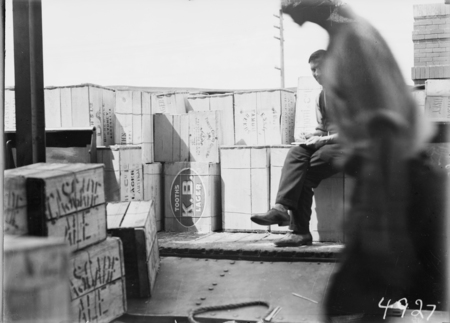 First consignment of liquor following the lifting of Probition in the ACT. Railway truck load of beer cases with a tally clerk.