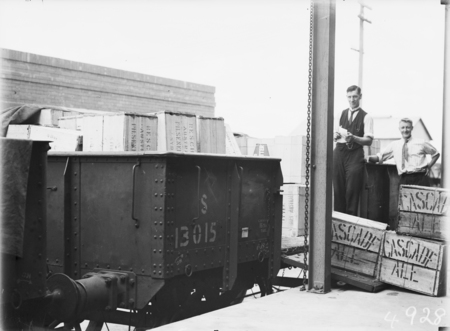 First consignment of liquor following the lifting of Probition in the ACT. Railway  truck load of beer cases being unloaded and the tally clerk.