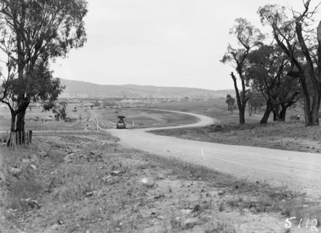 Duntroon Road now Fairbairn Avenue, Campbell, looking towards Reid with road roller. Site of the War Memorial on the left.