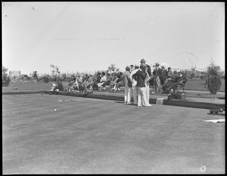 Game of bowls in progress at Hotel Canberra with Parliament House in the background.