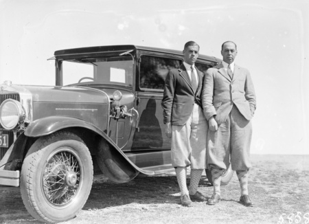 Two golfers with motor car.