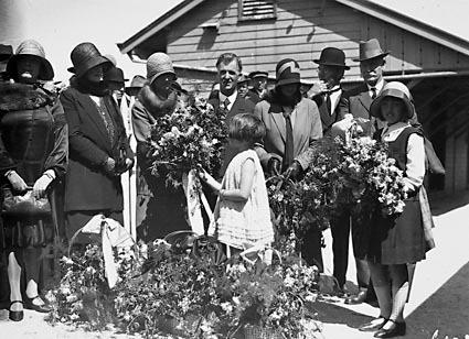 Mrs Scullin being presented with flower bouquets by children on Canberra railway station