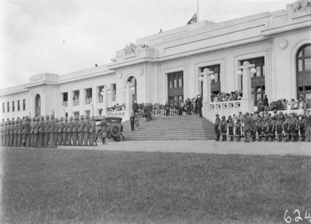 Armistice Day Ceremony with the Royal Military College Cadets on parade in front of Parliament House. Boy Scouts on the right. View from Parkes Place.