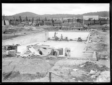 Manuka swimming pool under construction. Wall tiles being installed. Manuka Circle, Kingston.