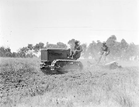 Crawler tractor pulling a tandem disc plough.