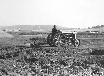 Fordson wheeled tractor hauling a scoop