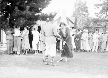 Group of spectators at the opening of a new Golf Club House. Lady Isaacs, wife of the Govenor  General, is pictured with the golf club.