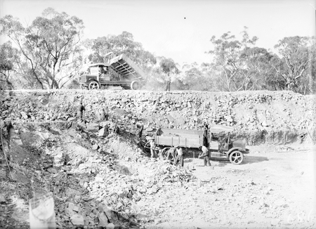 Workmen loading a truck in the excavation of the reservoir at Black Mountain. Second truck tipping spoil on the embankment.