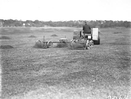 Tractor towing multiple lawn mowers on Royal Canberra golf course