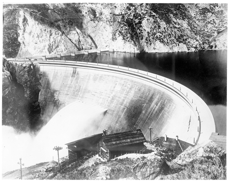 Photograph of picture of a concrete arch wall discharging water on a large dam.