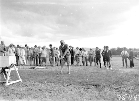 Opening of the extended Canberra Golf Course by Rt. Hon S. M. Bruce. Golfer preparing to tee off before spectators.