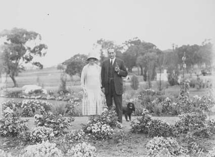Prime Minister, Right Honourable SM Bruce and Mrs Bruce, with pet dog, in gardens of The Lodge Adelaide Avenue, Deakin