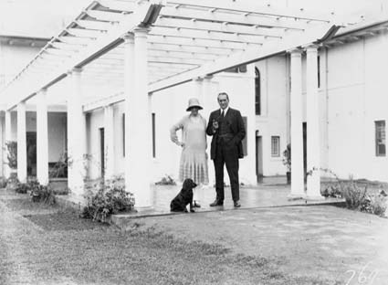 Prime Minister, Right Honourable SM Bruce and Mrs Bruce, with pet dog at the Pergola of the Lodge, Adelaide Avenue, Deakin